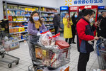 In this Jan. 22, 2020 photo, shoppers wear face masks as they line up at a grocery store in Wuhan in central China's Hubei Province. Complicated logistics are part of a daily flow of food and other goods authorities say is sustaining Wuhan and surrounding cities with a total of 50 million people. Most are blocked from leaving in the most sweeping disease-control measures ever imposed. (AP Photo/Arek Rataj)