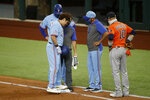 Texas Rangers' Shin-Soo Choo, left, is examined after falling at first base while trying to beat a throw while manager Chris Woodward, center, and Houston Astros first baseman Yuli Gurriel (10) standby during the first inning of a baseball game in Arlington, Texas, Sunday, Sept. 27, 2020. (AP Photo/Roger Steinman)