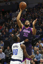 Minnesota Timberwolves' Karl-Anthony Towns, top, shoots over Dallas Mavericks' Harrison Barnes in the first half of an NBA basketball game Friday, Jan. 11, 2019, in Minneapolis. (AP Photo/Jim Mone)
