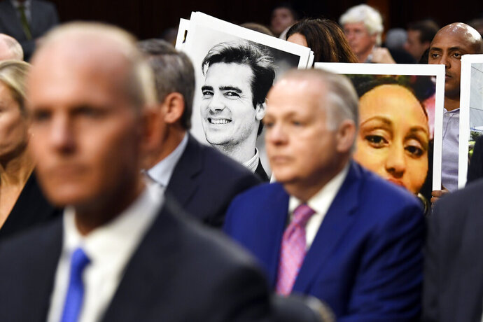People holding photos of those lost in Ethiopian Airlines Flight 302 and Lion Air Flight 610 listen as Boeing Company President and Chief Executive Officer Dennis Muilenburg, front left, waits to testify at a Senate Transportation Committee hearing on Capitol Hill in Washington, Tuesday, Oct. 29, 2019, about