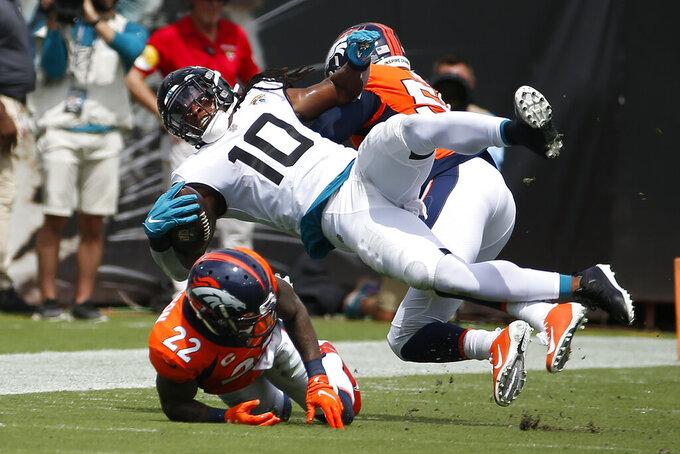 Jacksonville Jaguars wide receiver Laviska Shenault Jr. (10) is stopped by Denver Broncos safety Kareem Jackson (22) and linebacker Malik Reed, right, during the first half of an NFL football game, Sunday, Sept. 19, 2021, in Jacksonville, Fla. (AP Photo/Stephen B. Morton)