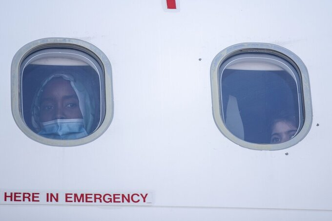 FILE - In this Friday, July 24, 2020 file photo, a young woman and a child look out of a window of a plane as group of 85 migrant children with health issues board a plane to Germany, at Athens International Airport. Five years on, the deal between European Union and Turkey is no longer working but at a summit next week EU leaders will discuss ways to improve relations with Turkey and could try to revive the agreement. (AP Photo/Petros Giannakouris, File)