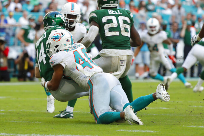 Miami Dolphins defensive back Nik Needham (40) sacks New York Jets quarterback Sam Darnold (14) during the second half of an NFL football game, Sunday, Nov. 3, 2019, in Miami Gardens, Fla. (AP Photo/Wilfredo Lee)