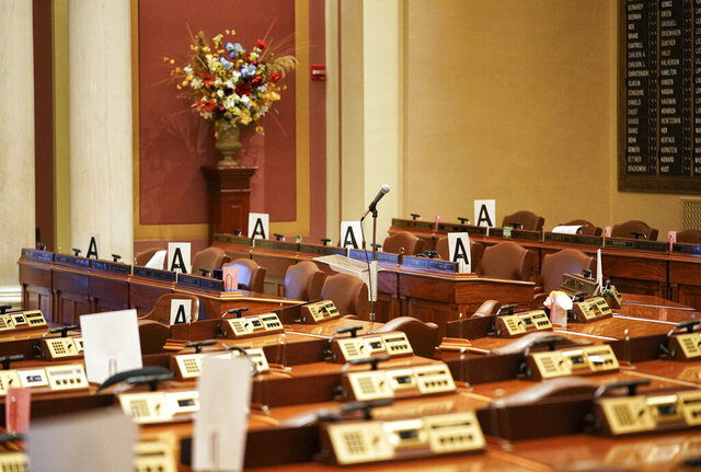 FILE - In this Wednesday, March 18, 2020 file photo, the House chamber at the state Capitol is empty in St. Paul, Minn., with some desks marked with an