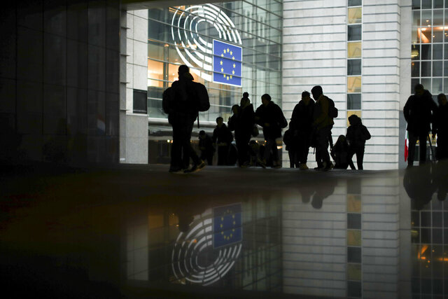 People walk past outside the European Parliament in Brussels, Friday, Jan. 24, 2020. The leaders of two of the European Union's main institutions on Friday signed the divorce agreement governing Britain's departure from the bloc next week, sealing the penultimate step in Brexit at a ceremony held without media access. (AP Photo/Francisco Seco)