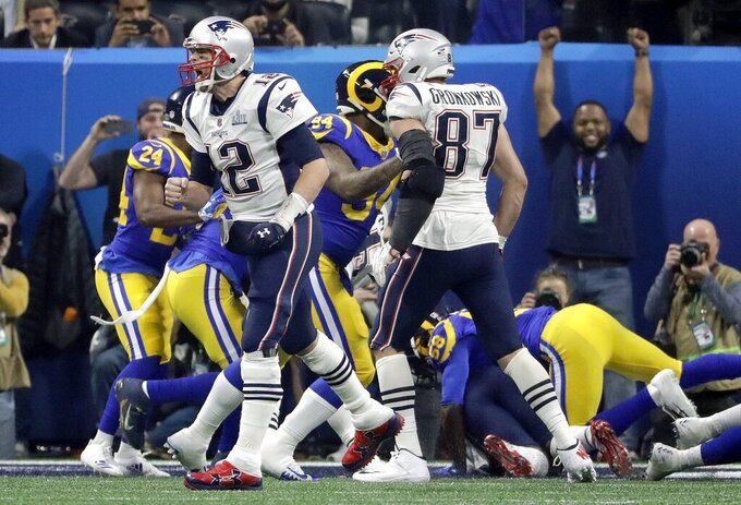 New England Patriots' Tom Brady (12) celebrates a touchdown run by Sony Michel during the second half of the NFL Super Bowl 53 football game against the Los Angeles Rams, Sunday, Feb. 3, 2019, in Atlanta. (AP Photo/Chuck Burton)