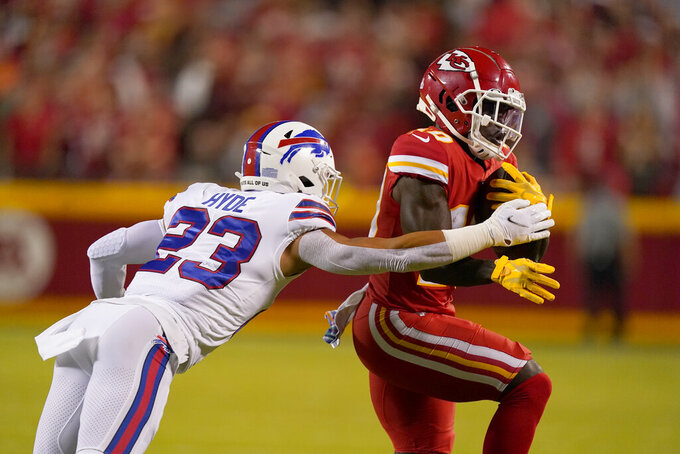 Kansas City Chiefs wide receiver Tyreek Hill, right, runs with the ball as Buffalo Bills safety Micah Hyde defends during the first half of an NFL football game Sunday, Oct. 10, 2021, in Kansas City, Mo. (AP Photo/Charlie Riedel)