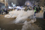 Tear gas fills the street as protesters continue to battle with police on the streets of Hong Kong on Saturday, Sept. 21, 2019. Protesters in Hong Kong threw gasoline bombs and police fired tear gas Saturday in renewed clashes over anti-government grievances (AP Photo/Kin Cheung)