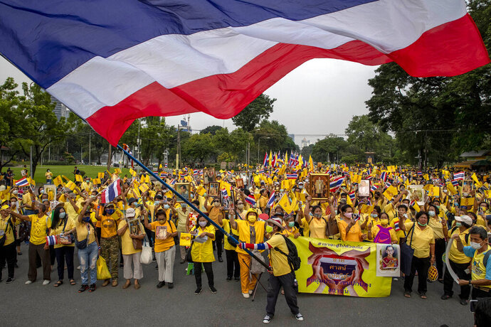 Supporters of the Thai monarchy display images of King Maha Vajiralongkorn, Queen Suthida, late King Bhumibol Adulyadej and wave a giant national flag during a rally at Lumphini park in central Bangkok, Thailand Tuesday, Oct. 27, 2020. Hundreds of royalists gathered to oppose pro-democracy protesters' demands that the prime minister resign, constitution be revised and the monarchy be reformed in accordance with democratic principles. (AP Photo/Gemunu Amarasinghe)