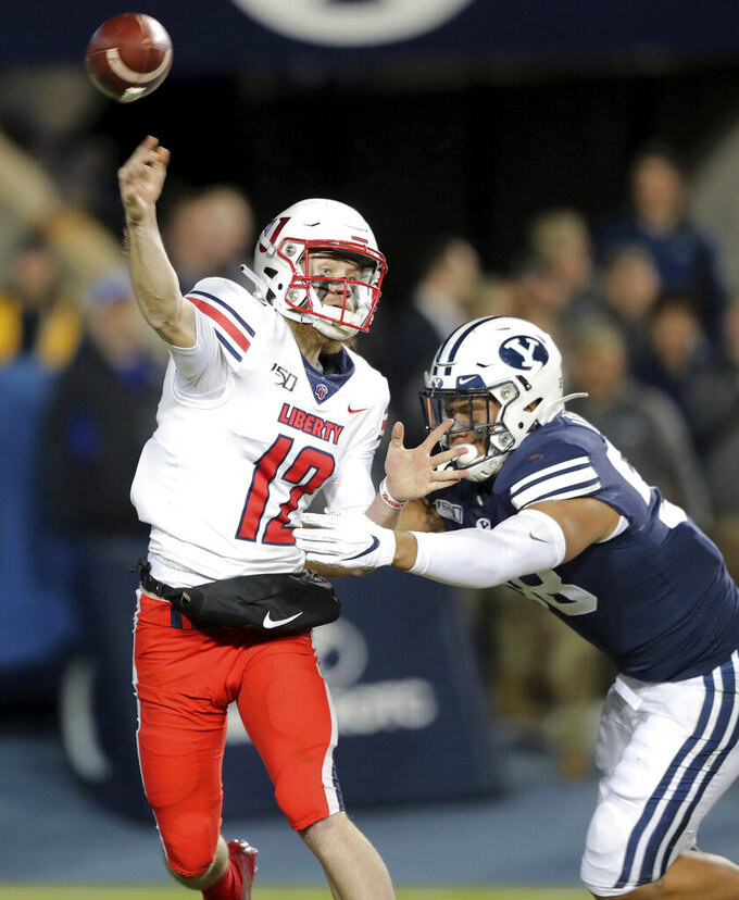 Liberty quarterback Stephen Calvert (12) throws a pass as he is hit by BYU defensive lineman Uriah Leiataua (58) during an NCAA college football Saturday, Nov. 9, 2019, in Provo, Utah. BYU won 31-24. (Scott G Winterton/The Deseret News via AP)