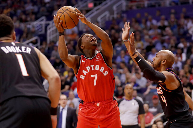Toronto Raptors guard Kyle Lowry (7) shoots over Phoenix Suns guard Jevon Carter (4) during the first half of an NBA basketball game Tuesday, March 3, 2020, in Phoenix.(AP Photo/Matt York)