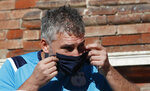 Mattia Maestri adjusts his face mask prior to the start of a 180-kilometer relay race, in Codogno, Italy, Saturday, Sept. 26, 2020. Italy's coronavirus Patient No. 1, whose case confirmed one of the world's deadliest outbreaks was underway, is taking part in a 180-kilometer relay race as a sign of hope for COVID victims after he himself recovered from weeks in intensive care. Mattia Maestri, a 38-year-old Unilever manager, was suited up Saturday for the start of the two-day race between Italy's first two virus hotspots. It began in Codogno, where Maestri tested positive Feb. 21, and was ending Sunday in Vo'Euganeo, where Italy's first official COVID death was recorded the same day. (AP Photo/Antonio Calanni)