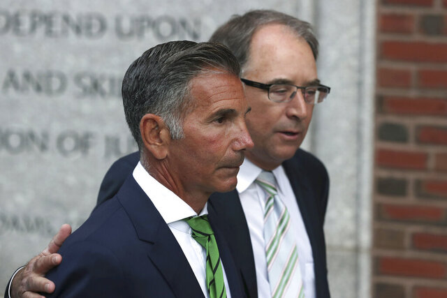 FILE - Clothing designer Mossimo Giannulli, foreground, departs federal court in Boston on Wednesday, April 3, 2019, after facing charges in a nationwide college admissions bribery scandal. Giannulli is asking to serve the remainder of his five-month prison term at home, saying he spent eight weeks in solitary confinement before being transferred to a minimum security camp this week. Giannulli's lawyers said Thursday, Jan. 14, 2021 that Giannulli believed he would only be held in quarantine for a short time before testing negative for the coronavirus. (AP Photo/Charles Krupa, File)