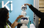People touch Kiki robots at the Zoetic AI booth at CES International, Wednesday, Jan. 9, 2019, in Las Vegas. (AP Photo/John Locher)