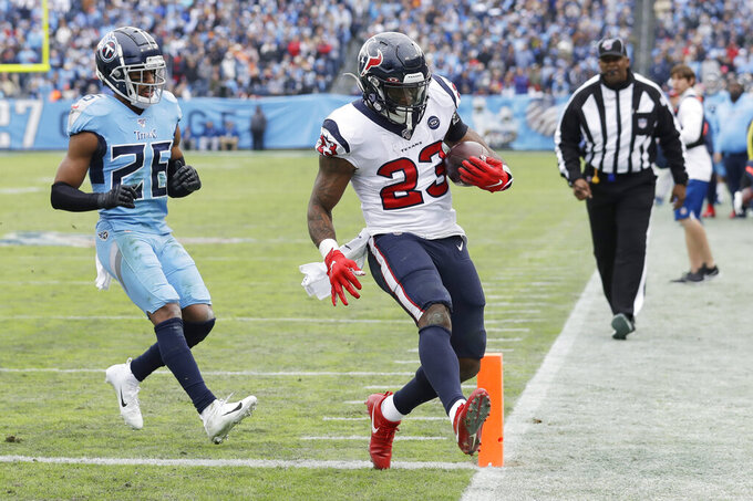 Houston Texans running back Carlos Hyde (23) beats Tennessee Titans cornerback Logan Ryan (26) to the end zone as Hyde scores a touchdown on a 10-yard run in the second half of an NFL football game Sunday, Dec. 15, 2019, in Nashville, Tenn. (AP Photo/James Kenney)