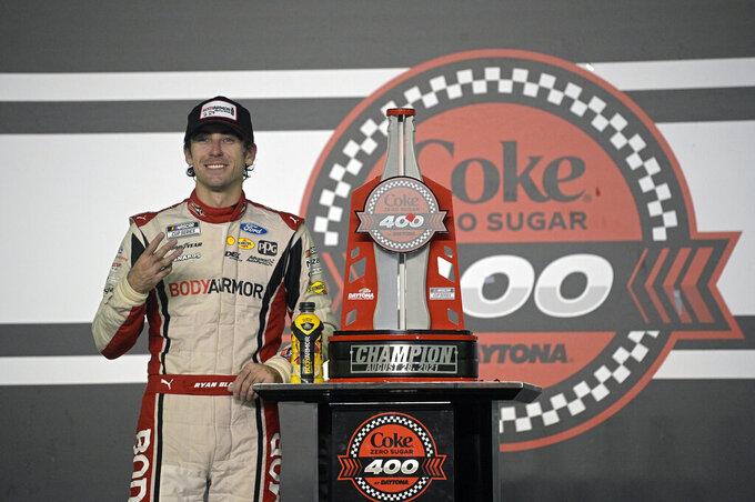 Ryan Blaney poses with the champion trophy in Victory Lane after winning a NASCAR Cup Series auto race at Daytona International Speedway, Saturday, Aug. 28, 2021, in Daytona Beach, Fla. (AP Photo/Phelan M. Ebenhack)