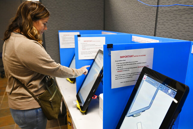 FILE - In this Tuesday, Nov. 5, 2019, file photo, Courtney Parker votes on a new voting machine in Dallas, Ga. In a ruling issued on Sunday, Oct. 11, 2020, a federal judge expressed serious concerns about the new election system but declined to immediately order the state to switch to hand-marked ballots so close to the November 2020 election. (AP Photo/Mike Stewart, File)