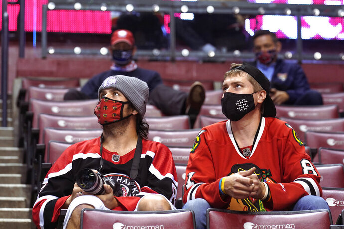 Chicago Blackhawk fans watch during the second period of the team's NHL hockey game against the Florida Panthers on Tuesday, Jan. 19, 2021, in Sunrise, Fla. The Panthers allow a limited number of fans to attend their games. Not only are the Panthers still unbeaten after two games — just the sixth time in the franchise's 27-year history that has happened — but they're also leading the NHL in attendance. (AP Photo/Marta Lavandier)