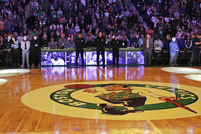 Fans stand during a tribute to the late Los Angeles Laker Kobe Bryant, before an NBA basketball between the Boston Celtics and the Golden State Warriors, Thursday, Jan. 30, 2020, in Boston. (AP Photo/Elise Amendola)