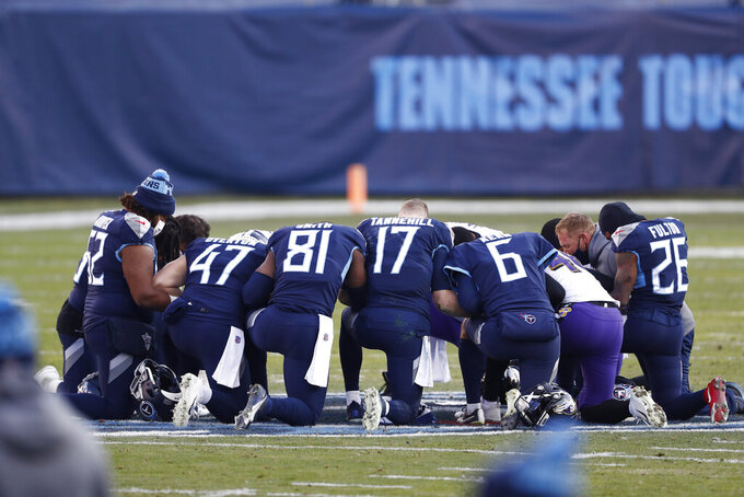Tennessee Titans players pray on the field after losing to the Baltimore Ravens in an NFL wild-card playoff football game Sunday, Jan. 10, 2021, in Nashville, Tenn. The Ravens won 20-13. (AP Photo/Wade Payne)