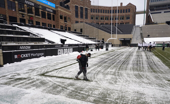 A field worker uses a blower to cut through the snow and create the sideline in Folsom Field in sub-freezing temperatures and light snow before the first half of an NCAA college football game as Colorado hosts Utah Saturday, Dec. 12, 2020, in Boulder, Colo. (AP Photo/David Zalubowski)