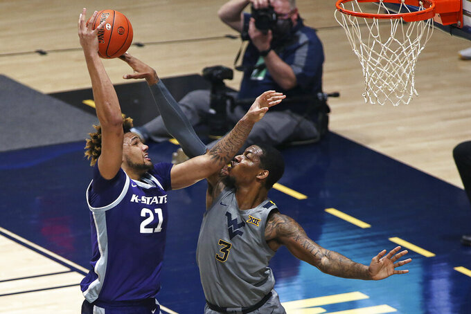 West Virginia forward Gabe Osabuohien (3) is defended by Kansas State forward Davion Bradford (21) during the first half of an NCAA college basketball game Saturday, Feb. 27, 2021, in Morgantown, W.Va. (AP Photo/Kathleen Batten)
