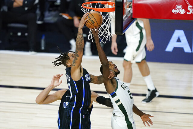 Orlando Magic's Markelle Fultz, left, fights for a rebound with Milwaukee Bucks' Khris Middleton during the second half of an NBA basketball first round playoff game Monday, Aug. 24, 2020, in Lake Buena Vista, Fla. (AP Photo/Ashley Landis, Pool)
