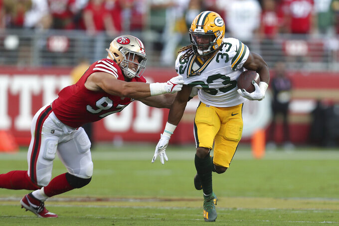 San Francisco 49ers defensive end Nick Bosa, left, tackles Green Bay Packers running back Aaron Jonesduring the first half of an NFL football game in Santa Clara, Calif., Sunday, Sept. 26, 2021. (AP Photo/Jed Jacobsohn)