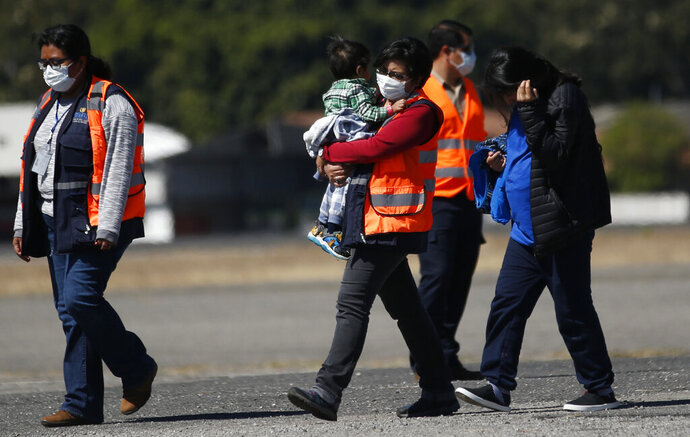 FILE - In this March 12, 2020 file photo, an immigration worker in an orange jacket and wearing a mask as a precaution against the spread of the new coronavirus, carries a young Guatemalan migrant who was deported from the U.S., followed by another deportee, at La Aurora International airport in Guatemala City. (AP Photo/Moises Castillo, File)