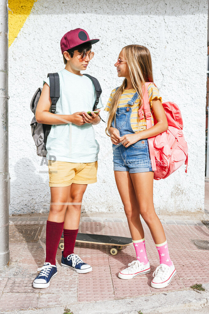 Male and female friends with backpacks talking while standing on footpath