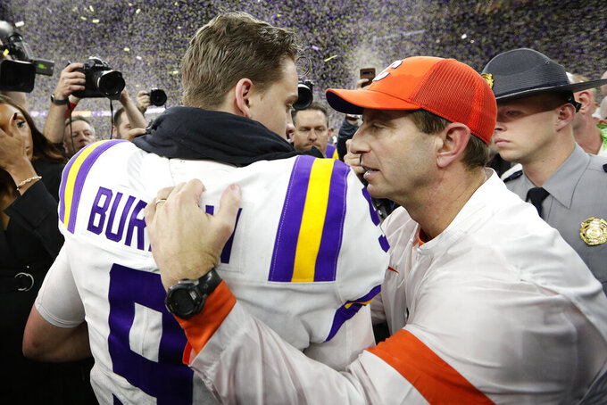 Clemson head coach Dabo Swinney, right, meets LSU quarterback Joe Burrow on the field after a NCAA College Football Playoff national championship game Monday, Jan. 13, 2020, in New Orleans. LSU won 42-25.(AP Photo/Sue Ogrocki)