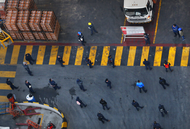 Employees of a bottled water company stand at a distance from each other as they prepare to distribute drinking water in Mexico City, Friday, May 8, 2020. Mexico woke up to news of its largest one-day increase in confirmed cases of COVID-19, from Wednesday to Thursday. (AP Photo/Marco Ugarte)