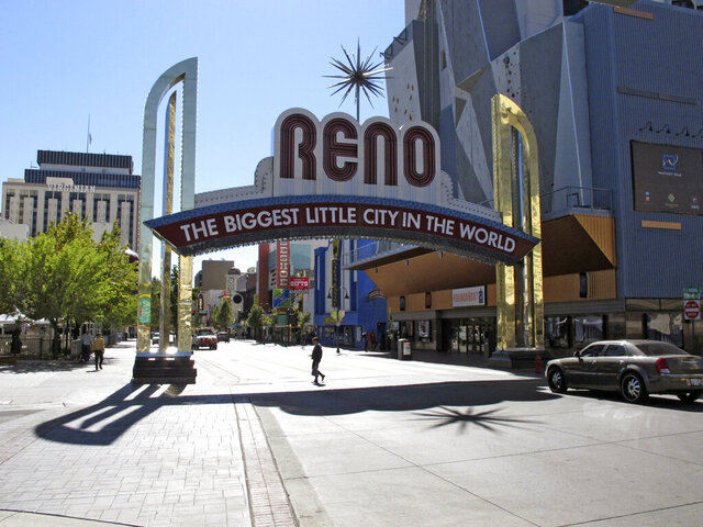 FILE - In this Oct. 11, 2016, file photo, pedestrians pass beneath the Reno arch as traffic passes on Virginia Street in downtown Reno, Nev. All bars, nightclubs, restaurants and gyms will close in Reno by 5 p.m. Friday, March 20, 2020, in an effort to reduce the risk of exposure to coronavirus, Mayor Hillary Schieve announced. Schieve initially included casinos on the closure list late Monday with plans to begin the shutdowns Tuesday morning. But she quickly rescinded that directive and further clarified restaurants can continue carry-out orders and keep drive-through windows open. (AP Photo/Scott Sonner, File)
