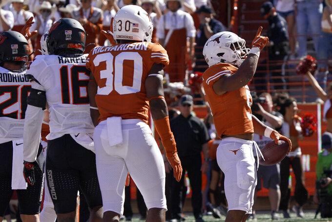 Texas running back Bijan Robinson (5) celebrates his touchdown run against Oklahoma State during the first half of an NCAA college football game in Austin, Texas, Saturday, Oct. 16, 2021. (AP Photo/Chuck Burton)