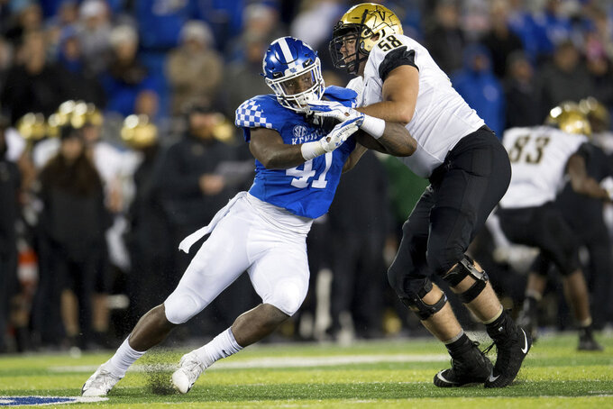 Kentucky linebacker Josh Allen (41) is held by Vanderbilt offensive lineman Justin Skule (58) during the second half of an NCAA college football game in Lexington, Ky., Saturday, Oct. 20, 2018. Kentucky won, 14-7. (AP Photo/Bryan Woolston)