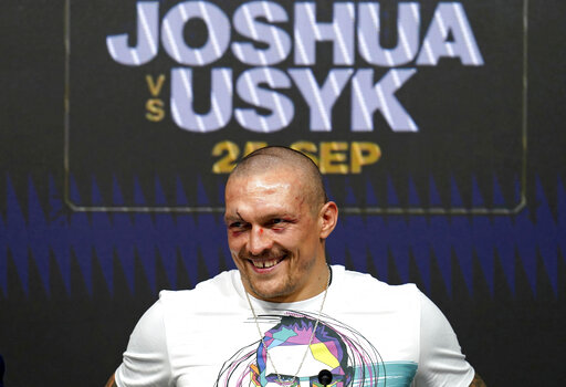 Oleksandr Usyk of Ukraine smiles during a press conference after winning the WBA (Super), WBO and IBF boxing title bout against Anthony Joshua of Britain at the Tottenham Hotspur Stadium in London Saturday Sept. 25, 2021. (Nick Potts/PA via AP)