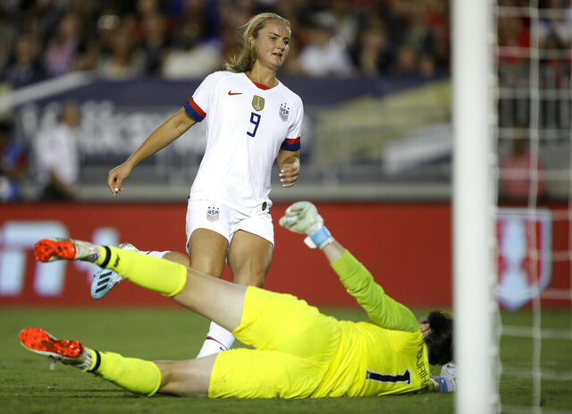 FILE - In this Aug. 3, 2019, file photo, United States midfielder Lindsey Horan, top, scores against Ireland goalkeeper Marie Hourihan during the first half of an international friendly soccer match in Pasadena, Calif. Horan described herself as miserable when she caught COVID-19 late last year. The 26-year-old midfielder was set to accompany the U.S. national team to the Netherlands for their final match of the year when U.S. Soccer announced her diagnosis on Nov. 18. (AP Photo/Alex Gallardo, File)