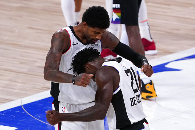 Los Angeles Clippers' Patrick Beverley (21) reacts to winning the game with teammate Paul George, left, after their game with their NBA conference semifinal playoff basketball game with the Denver Nuggets Monday, Sept. 7, 2020, in Lake Buena Vista, Fla. LA defeated the Nuggets 113-107. (AP Photo/Mark J. Terrill)