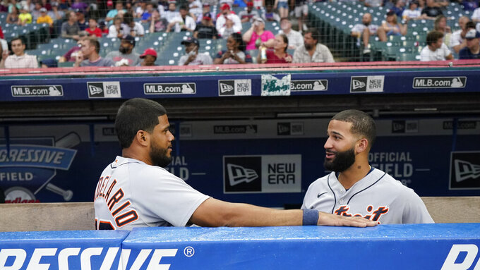 Detroit Tigers' Jeimer Candelario, left, and Nomar Mazara talk during a rain delay before a baseball game against the Cleveland Indians, Tuesday, June 29, 2021, in Cleveland. (AP Photo/Tony Dejak)