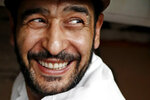 In this June 17, 2019, photo, Diaa Alhanoun, a Syrian refugee chef, smiles broadly while grinding meat in preparation for the 2019 Refugee Food Festival at Porsena, an East Village Italian restaurant, in New York. A festival veteran, Alhanoun participated for his second year along with other refugee chefs from Eat Offbeat who served meals at other local New York restaurants. Eat Offbeat is a refugee-staffed catering company where Alhanoun worked before opening his own restaurant. (AP Photo/Kathy Willens)