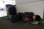Ezra Allen sleeps while waiting to board a flight to Tampa Bay at San Francisco International Airport in San Francisco, Tuesday, Nov. 26, 2019. Northern California and southern Oregon residents are bracing for a 'bomb cyclone' that's expected at one of the busiest travel times of the year. (AP Photo/Jeff Chiu)