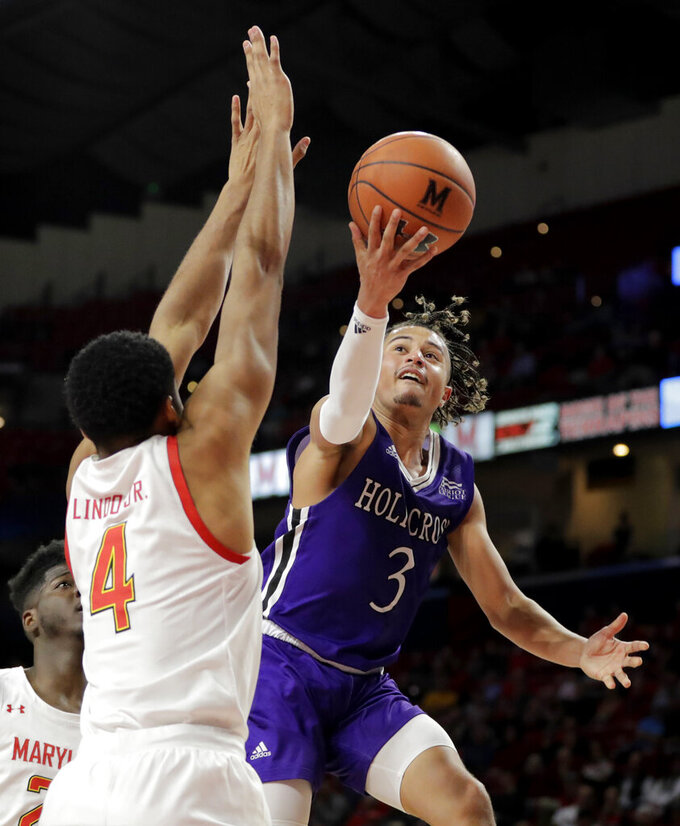 Holy Cross guard Drew Lowder (3) goes up for a shot against Maryland forward Ricky Lindo Jr. (4) during the second half of an NCAA college basketball game, Tuesday, Nov. 5, 2019, in College Park, Md. Maryland won 95-71. (AP Photo/Julio Cortez)