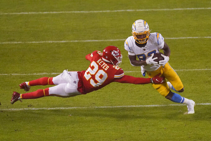 Los Angeles Chargers wide receiver Tyron Johnson breaks a tackle by Kansas City Chiefs cornerback Bopete Keyes (29) during the second half of an NFL football game, Sunday, Jan. 3, 2021, in Kansas City. (AP Photo/Charlie Riedel)