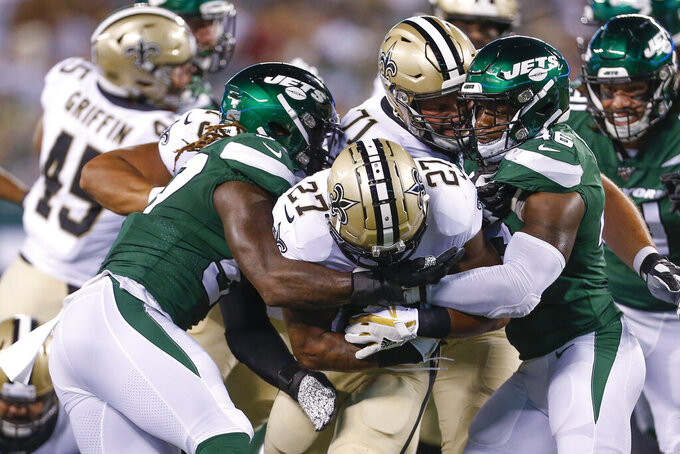 New Orleans Saints' Dwayne Washington (27) is tackled by New York Jets' Neville Hewitt, right, and C.J. Mosley, left, during the first half of a preseason NFL football game Saturday, Aug. 24, 2019, in East Rutherford, N.J. (AP Photo/Adam Hunger)