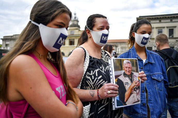 Members of Noi Denunceremo (We will denounce) group arrive at Bergamo's court, Italy, Monday, July 13, 2020. Lawyers for the Noi Denunceremo (We Will Denounce) Facebook group and an affiliated non-profit committee are filing 100 new cases Monday with Bergamo prosecutors investigating the outbreak, on top of 50 complaints lodged last month. ( Claudio Furlan/LaPresse via AP)