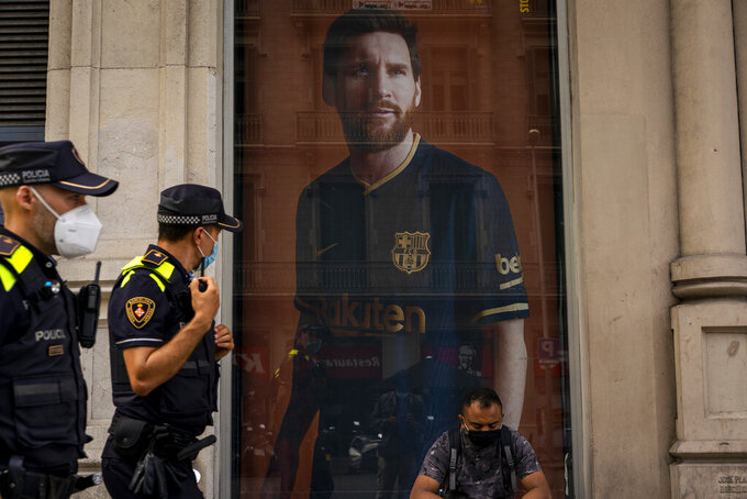 A poster with the face of Barcelona soccer player Lionel Messi is displayed at a F.C. Barcelona store in Barcelona, Spain on Tuesday, Sept. 1, 2020. Barcelona is banking on a face-to-face meeting with Lionel Messi to try to convince him to stay. Talks with Messi's father-agent are expected this week in Barcelona but the club also hopes to sit down with the player himself. (AP Photo/Emilio Morenatti)