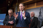 Senate Finance ranking member Ron Wyden, D-Ore., center, flanked by Senate Minority Leader Chuck Schumer, D-N.Y., left, and Senate Budget Committee Ranking Member Bernie Sanders, I-Vt., speaks to reporters during a news conference to criticize President Donald Trump's tax cuts and call for putting government funds toward a $1 trillion infrastructure package, at the Capitol in Washington, Wednesday, March 7, 2018. (AP Photo/J. Scott Applewhite)