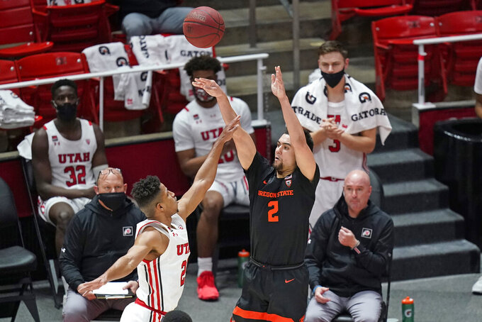 Oregon State guard Jarod Lucas (2) shoots as Utah guard Alfonso Plummer, left, defends during the first half of an NCAA college basketball game Wednesday, March 3, 2021, in Salt Lake City. (AP Photo/Rick Bowmer)