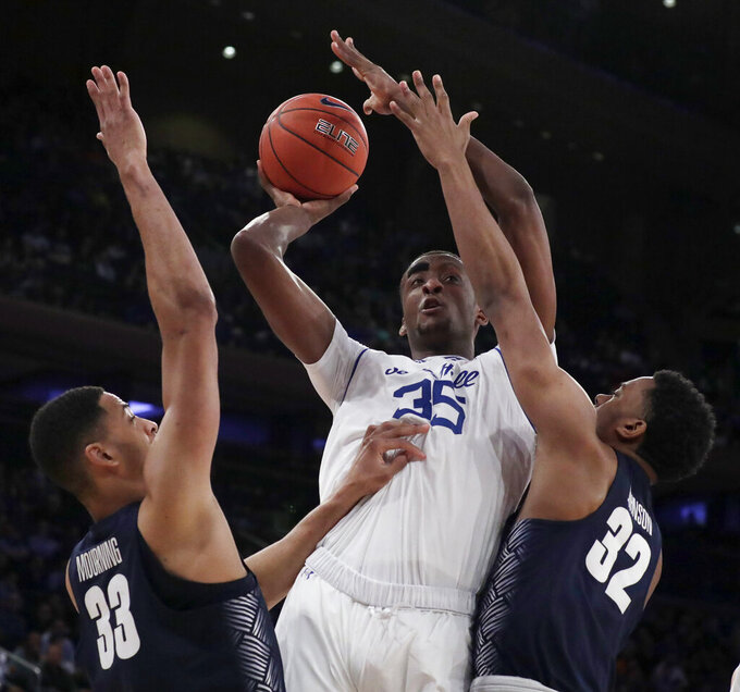 Seton Hall center Romaro Gill (35) goes up for a shot against Georgetown forward Trey Mourning (33) and guard Kaleb Johnson (32) during the first half of an NCAA college basketball game in the Big East men's tournament, Thursday, March 14, 2019, in New York. (AP Photo/Julio Cortez)
