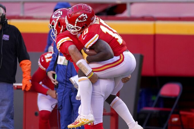 Kansas City Chiefs quarterback Patrick Mahomes, left, gives a ride on his back to wide receiver Tyreek Hill (10) after Hill scored a touchdown on a catch in the second half of an NFL football game against the New York Jets on Sunday, Nov. 1, 2020, in Kansas City, Mo. (AP Photo/Charlie Riedel)